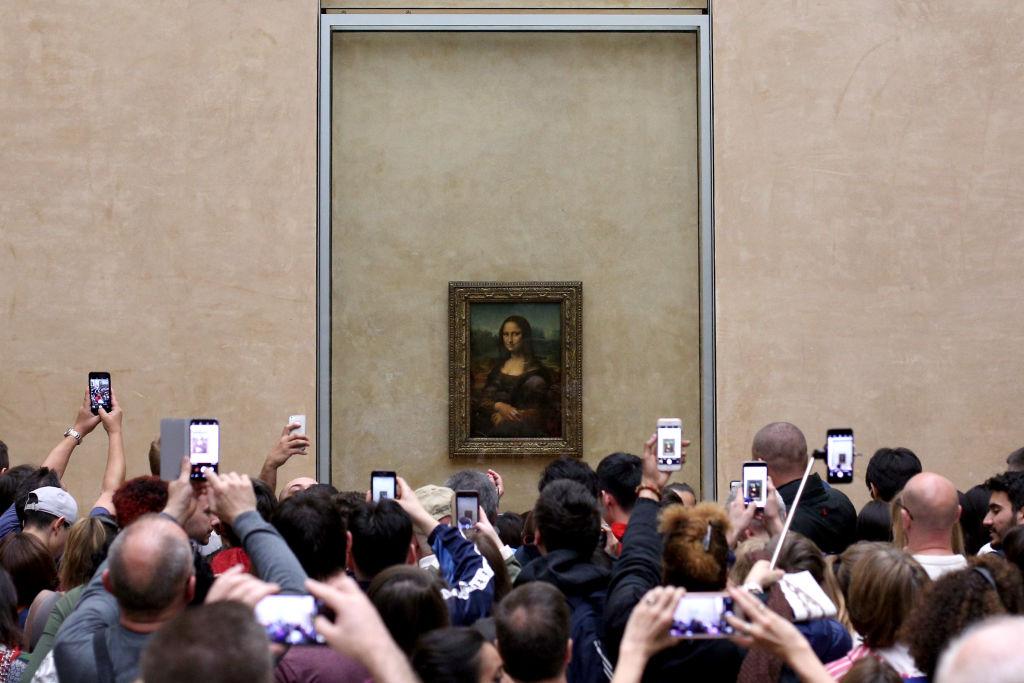 Visitors take pictures of 'La Joconde', a 1503-1506 oil on wood portrait of Mona Lisa by Leonardo Da Vinci, at the Louvre Museum in Paris,
