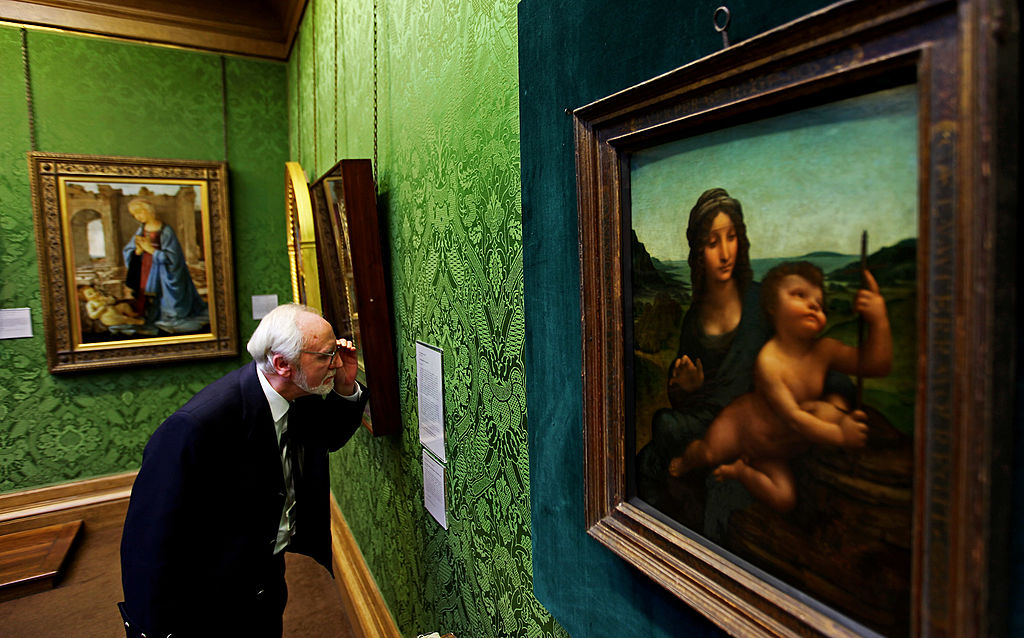 Joe Hay, security guard at the National Gallery of Scotland, stands beside the Leonardo da Vinci painting 'Madonna Of The Yarnwinder'