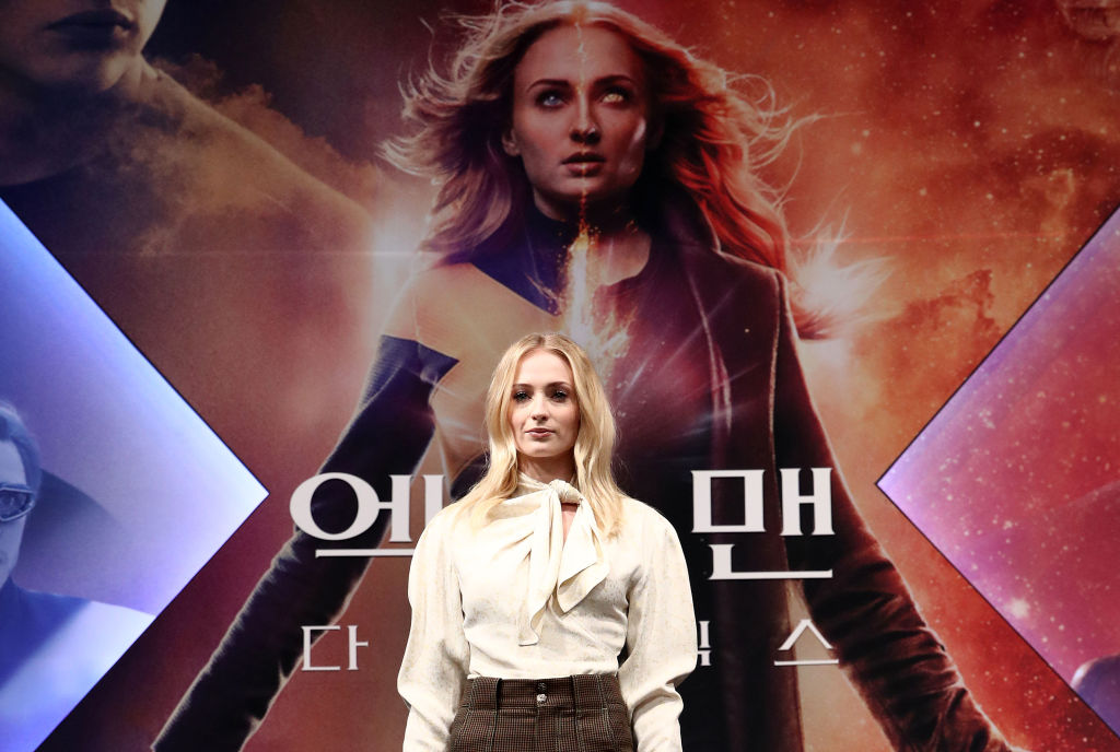 Sophie Turner posing in front of a poster of her playing Jean Grey the mutant
