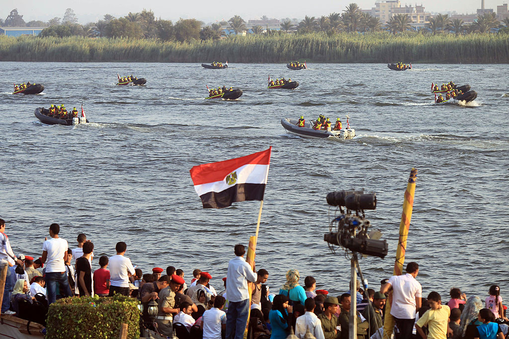 Egyptian spectators look at navy forces performing on the Nile in Cairo