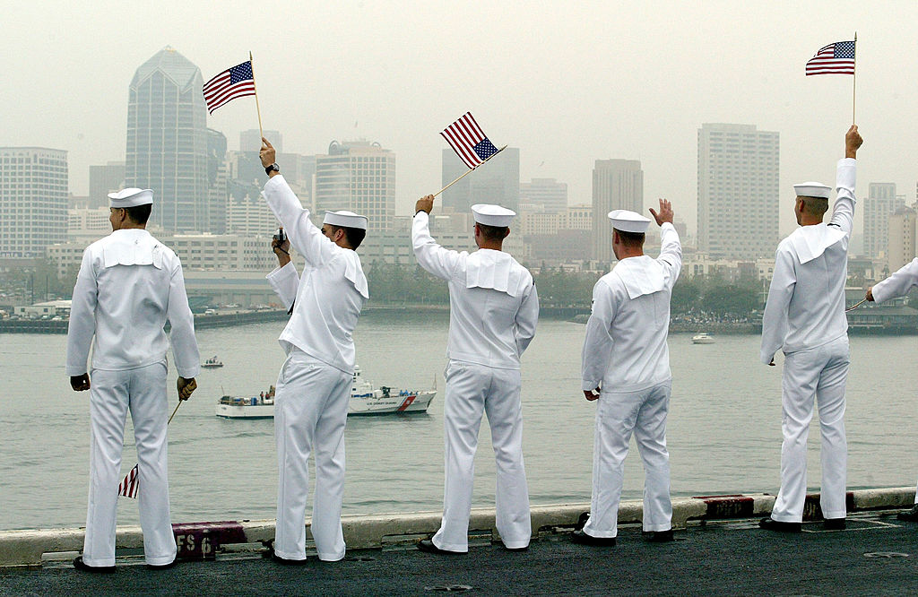 U.S. sailors wave to a passing boat while