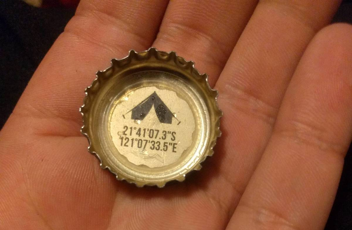 inside of a bottle cap with coordinates to a camp ground