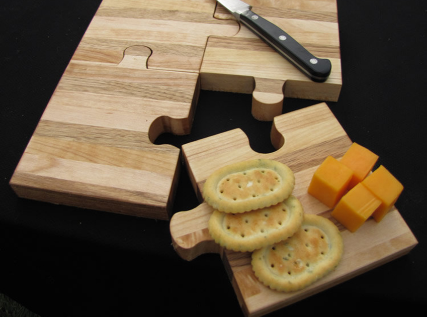 puzzle piece cutting board with crackers and cheese on one piece