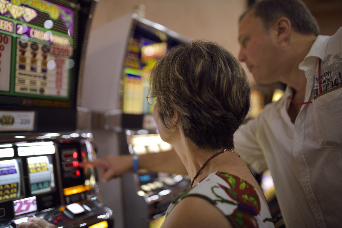 Man explaining readout to a woman on slot machines in a casino.