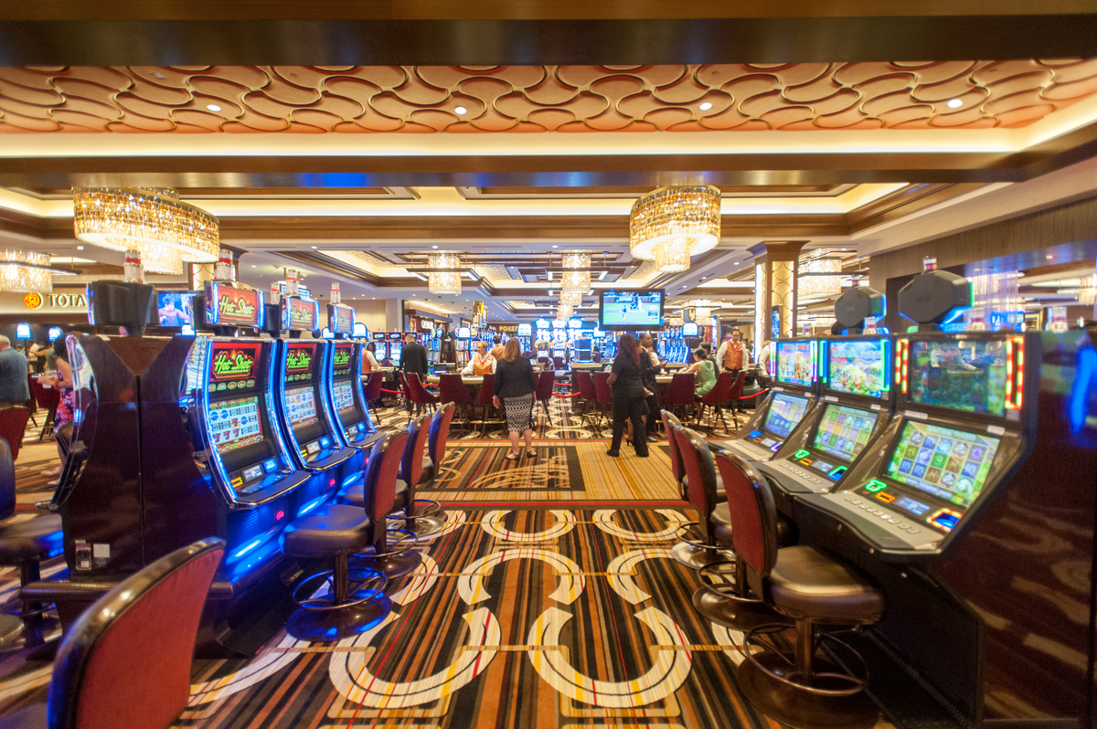Interior of people in casino gambling on slot machines.