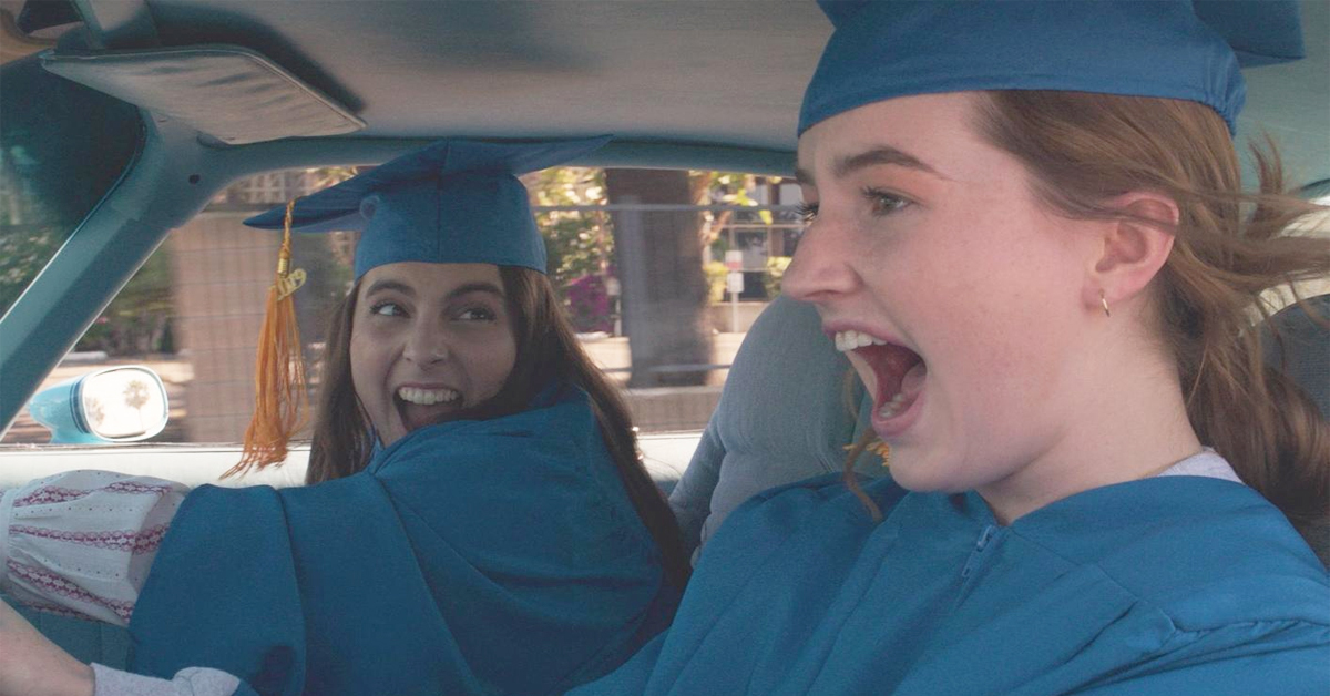 beanie feldstein and kaitlyn dever in graduation caps and gowns driving a car in booksmart
