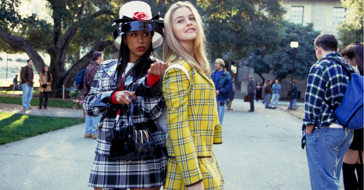 stacey dash and alicia silverstone in plaid outfits in front of a school in clueless