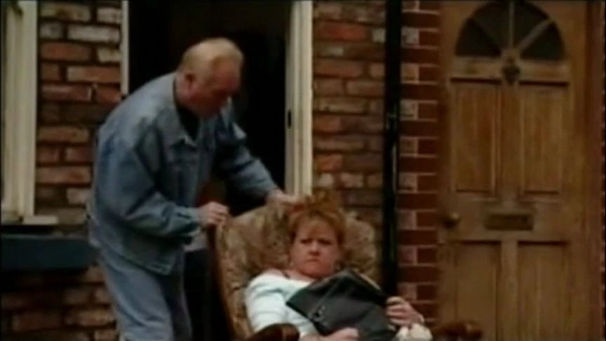 coronation street scene man behind lady in chair