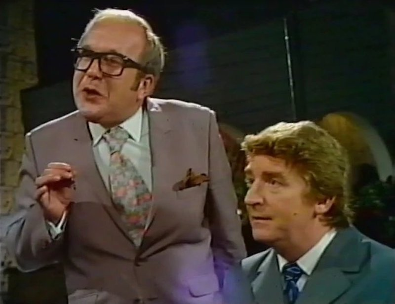 coronation street scene man with glasses and younger man