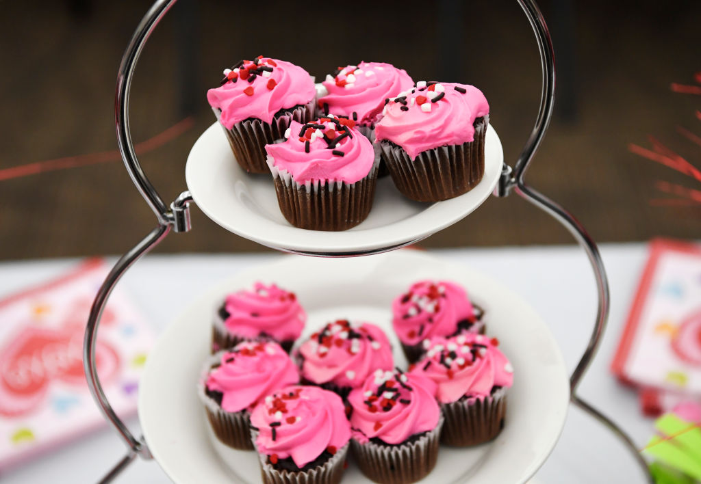 chocolate cupcakes with pink frosting and sprinkles on plates