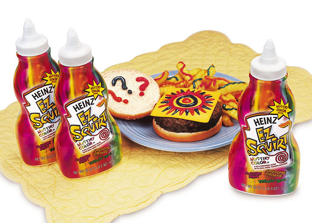 a few bottles of heinz ez squirt mystery color ketchup and a cheeseburger and fries on a placemat