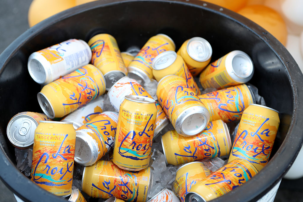 many cans of tangerine lacroix in a black ice bucket