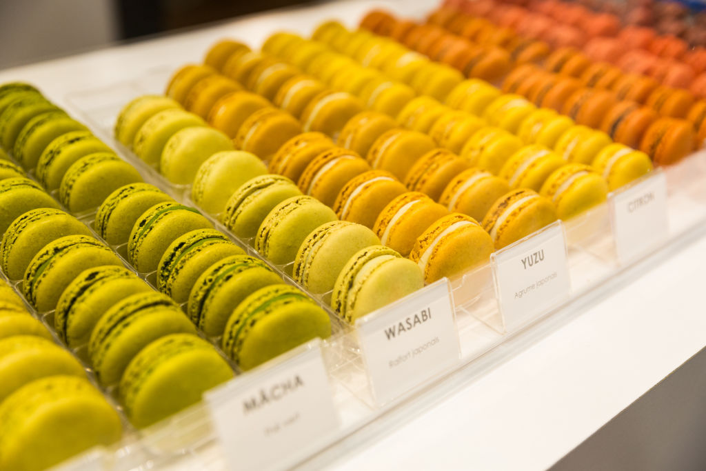 green, orange, yellow, and red macarons on a shelf