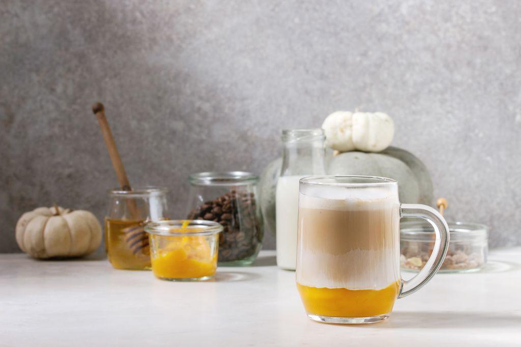 glass of pumpkin spice latte with pumpkin puree, milk foam, and cinnamon