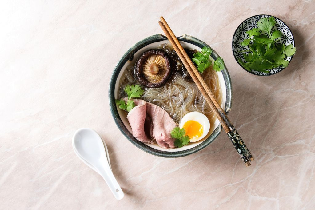a bowl of ramen with shiitake mushroom, egg, sliced beef, and greens