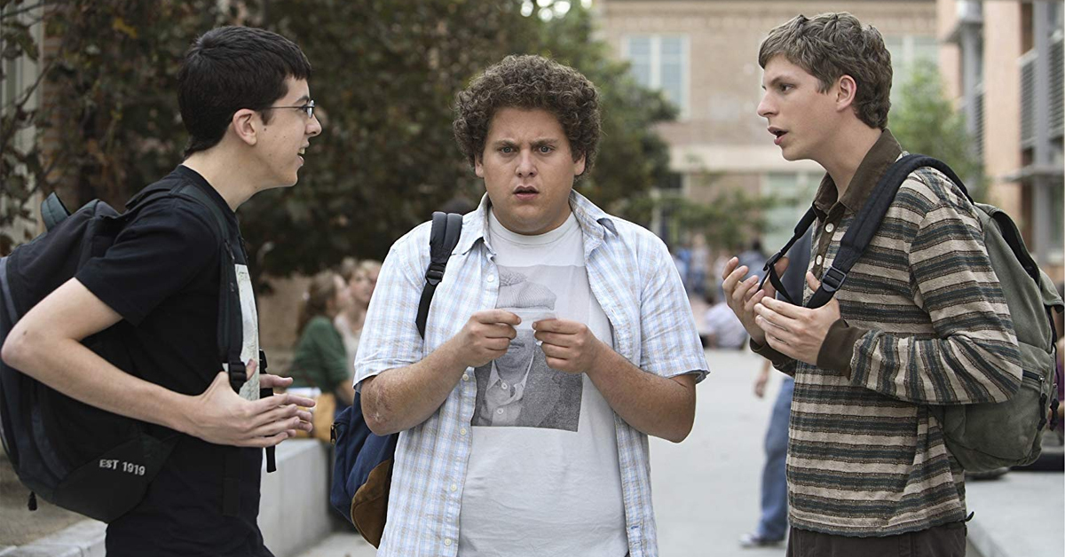 christopher mintz-plasse, jonah hill, and michael cera outside a school in superbad