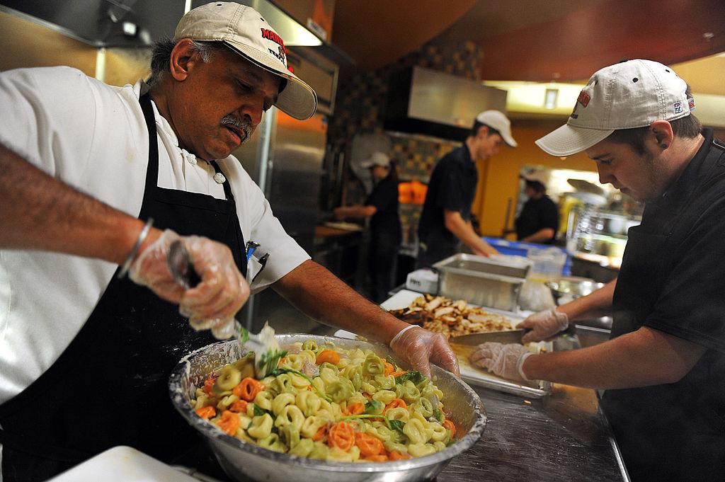 a man stirring a bowl of tri-color pasta tortellini