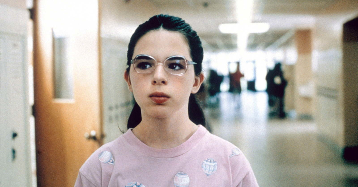 heather matarazzo wearing glasses and a pink shirt in a school hallway in welcome to the dollhouse