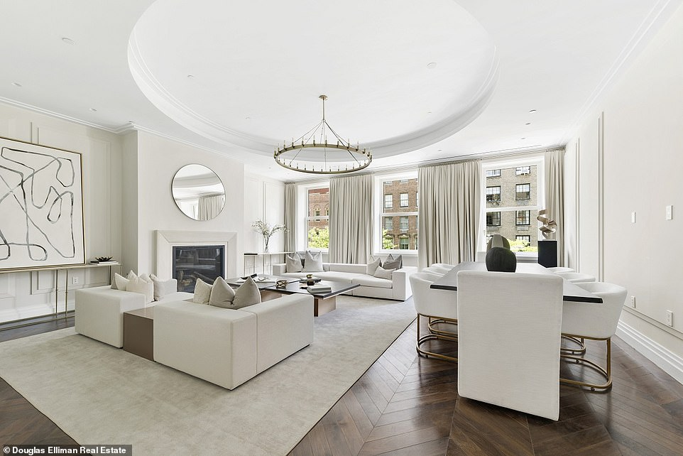A photgraph of one of the main living room shows white decor in a spacious room