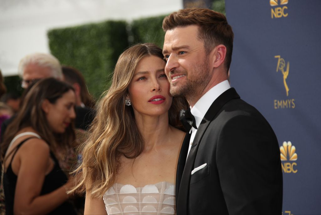 Jessica Biel looks earnestly at Justin Timberlake with he squints at the photographers.