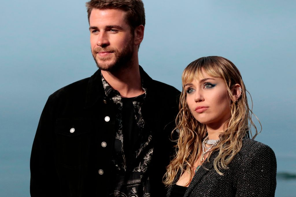 Miley Cyrus and Liam Hemsworth look somber while photographed at an event.