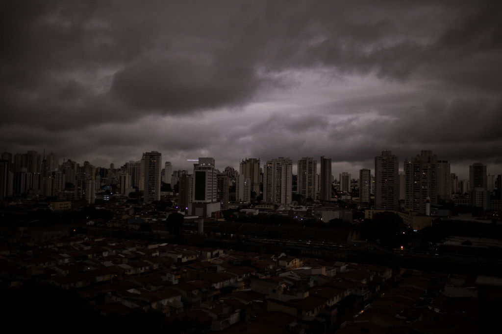 A view of São Paulo's skyscrapers shows dark grey skies over a nearly black city.