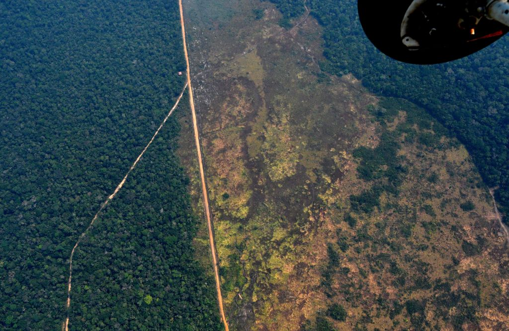 A helicopter shot reveals a large mass of land that has been deforested amongst the lush rainforest.