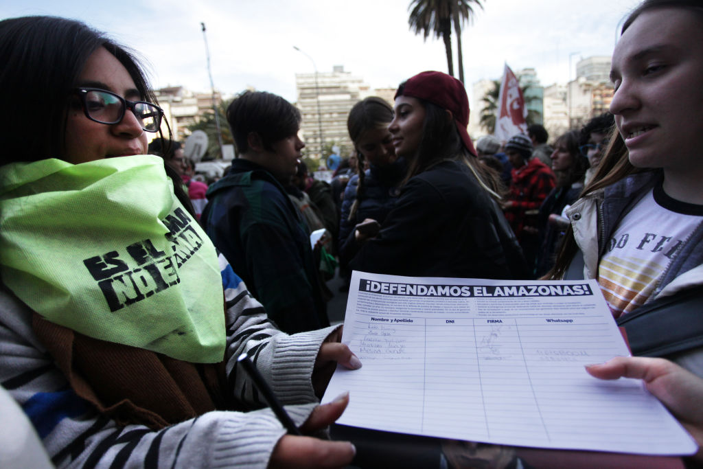 Young ladies in a crowd in Argentina hold a petition that reads
