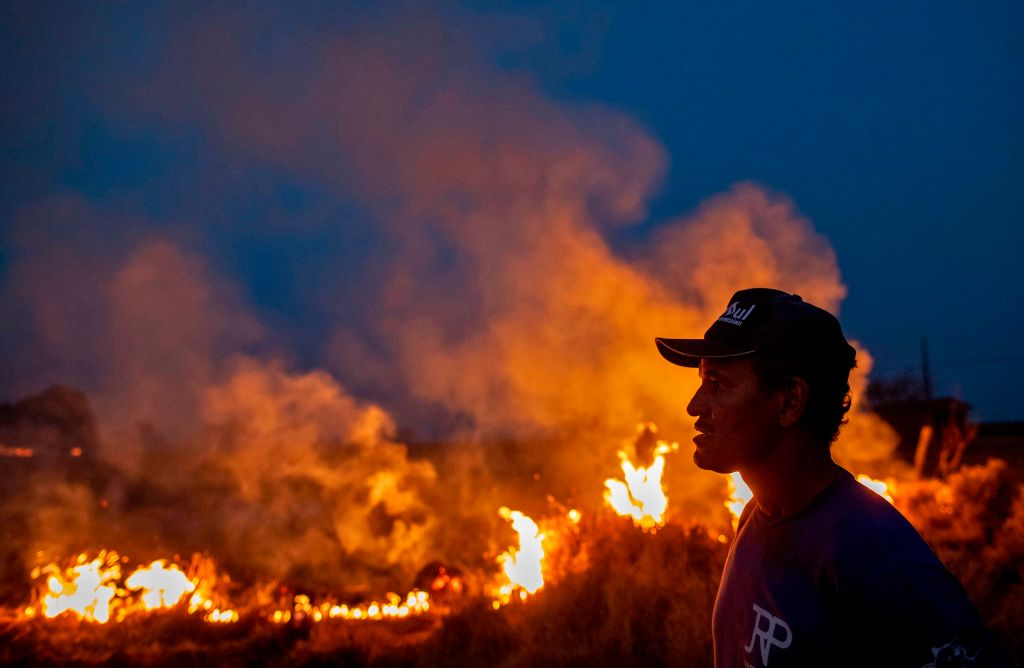 A profile shot of a laborer reveals flames engulfing the land before him.