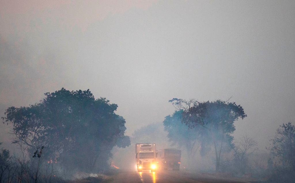 Trucks blare their headlights while driving down a densely smokey road.