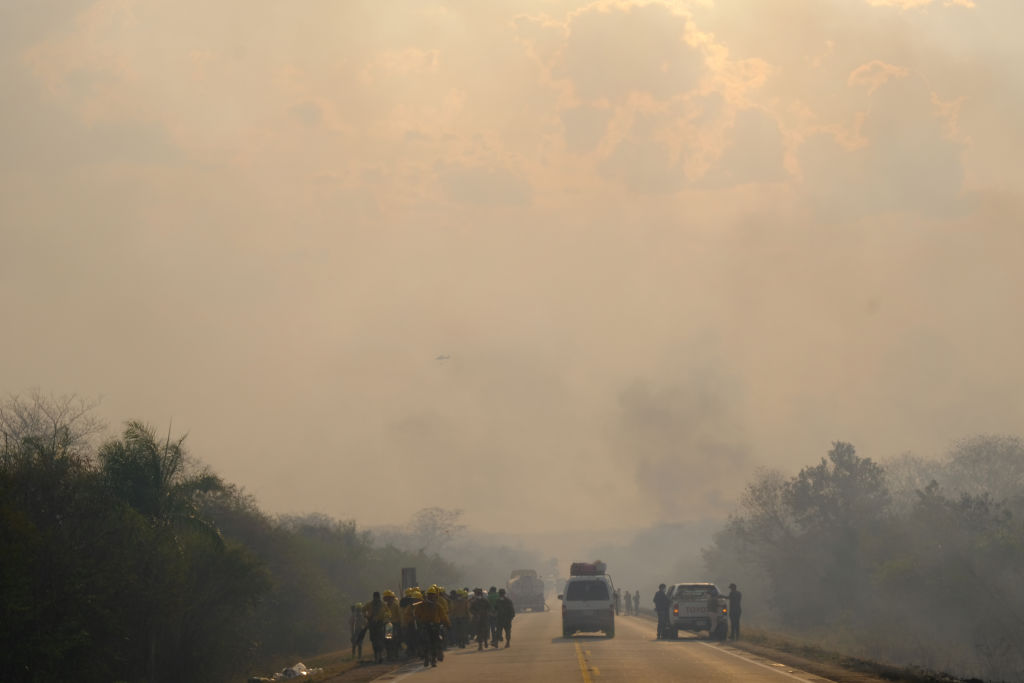 A road full of walking civilians and trucks is engulfed by thick smoke.