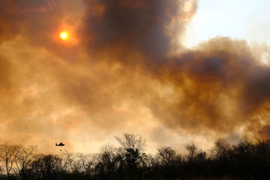 Heavy smoke blocks the sun as a silhouetted helicopter carries water towards the flames.