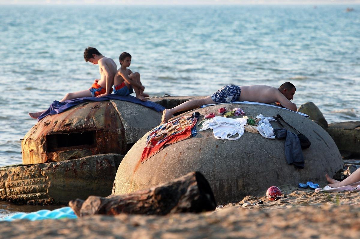 People sunbath atop of decrepit communist era bunkers on the shore in Qerret beach