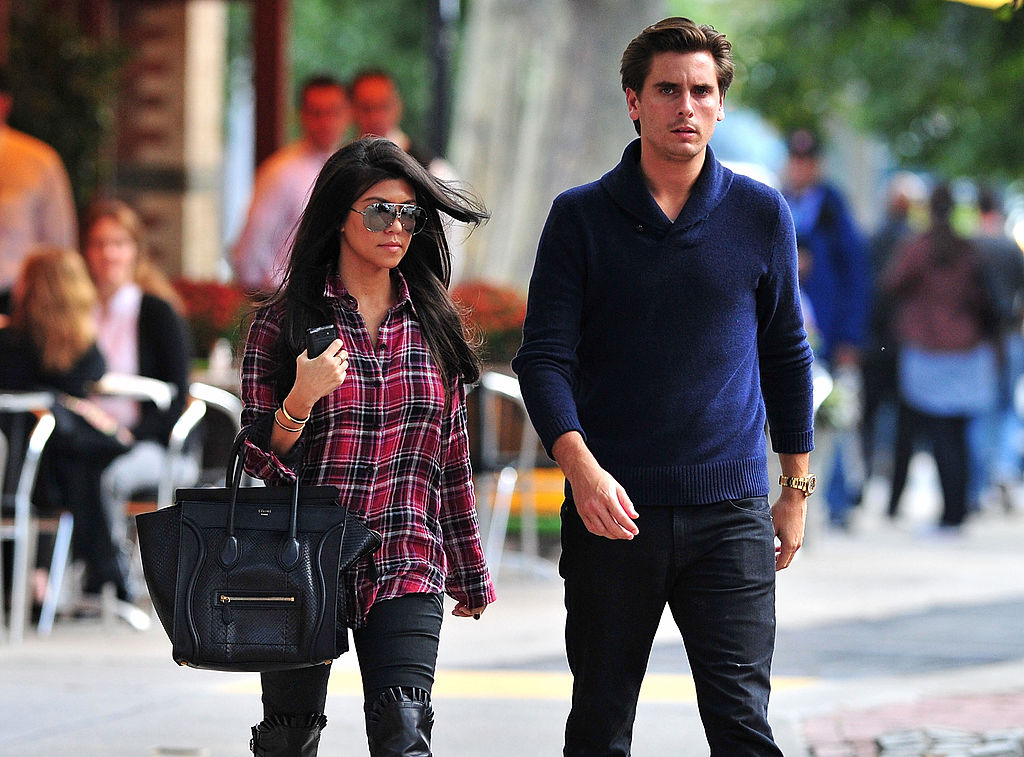 Scott Disick looks seriously at the camera while he and Kourtney Kardashian march down the sidewalk in LA.