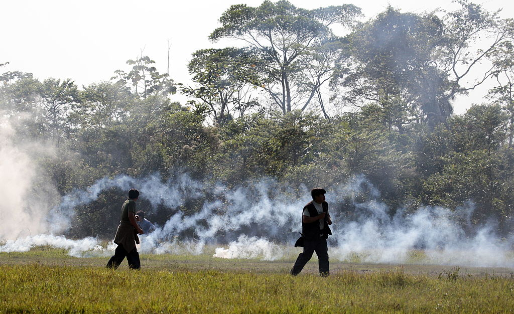 Two Bolivian protestors exit the rainforest amongst clouds of tear gas.