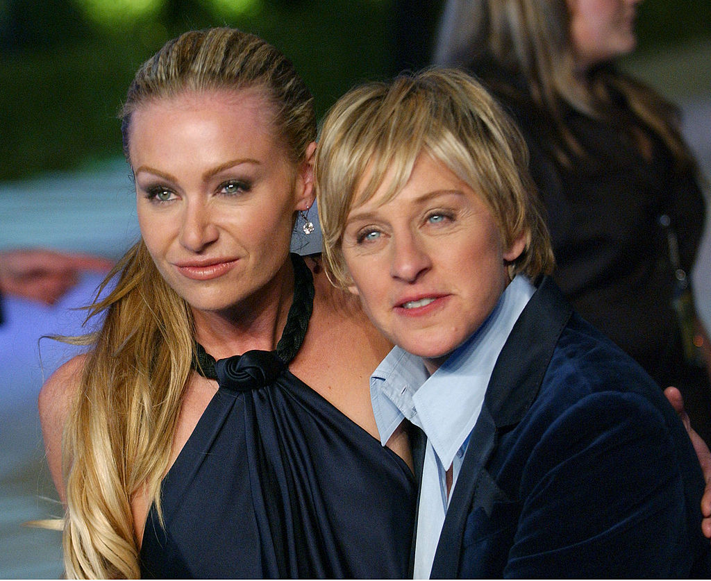Ellen DeGeneres looks severely out to a distance while Portia de Rossi purses her lips.