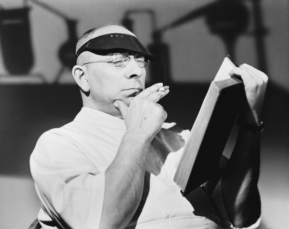 Wearing a sun visor, Austrian actor, screenwriter and director Erich von Stroheim (1885 - 1957) peruses a book during the filming of 'The Lady and the Monster'.