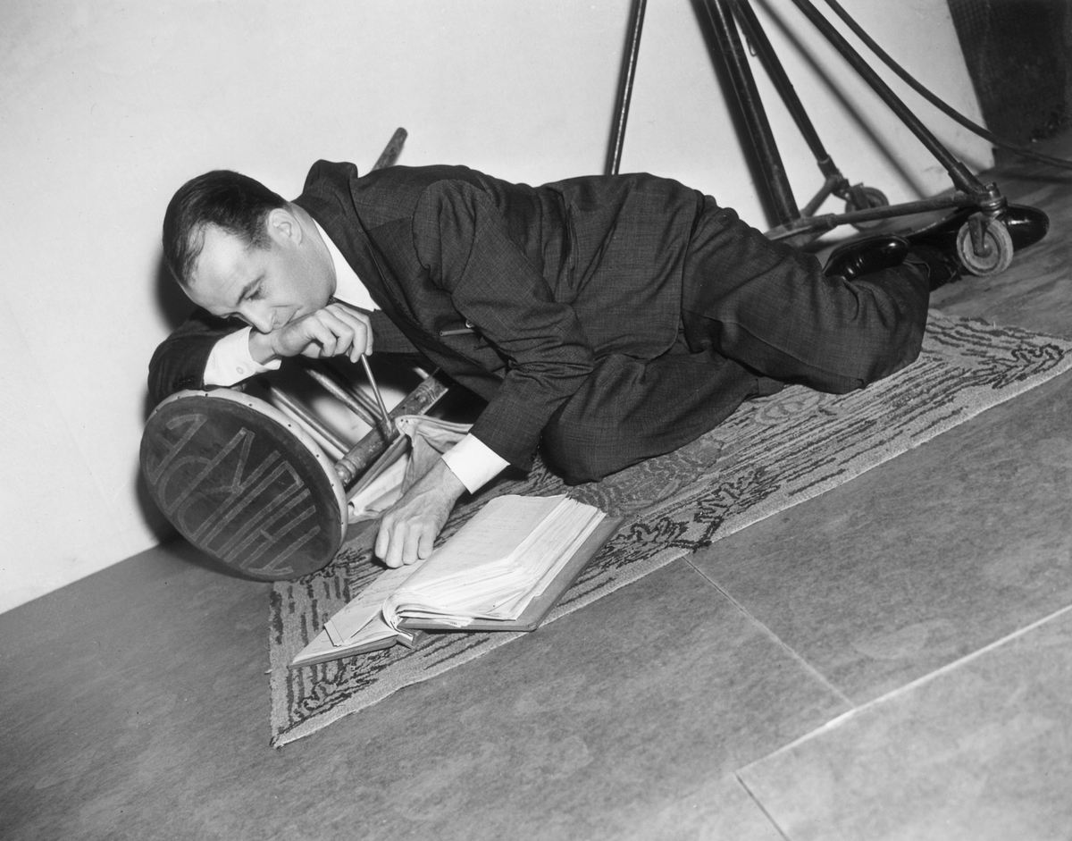 American film director Richard Thorpe reclines on the carpet, reading a script, while resting his chin on his hand.