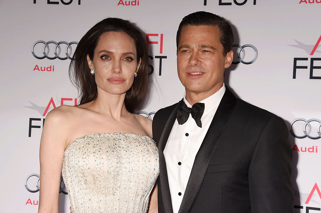 Angelina Jolie stares off into space while Brad Pitt smiles awkwardly at a premier.