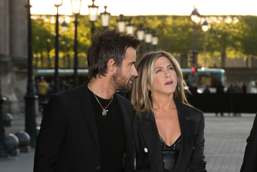 Justin Theroux seems to be saying something to Jennifer Aniston as she looks up with a confused expression.