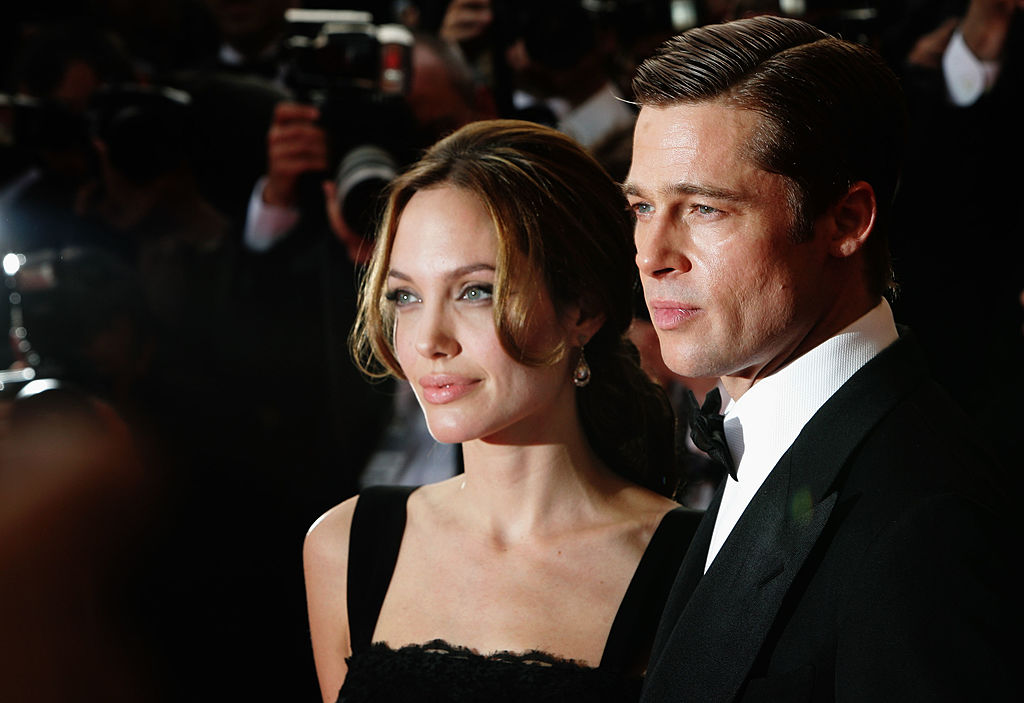 Angelina Jolie and Brad Pitt look in the same direction towards bright photography lights while dressed for Hollywood.