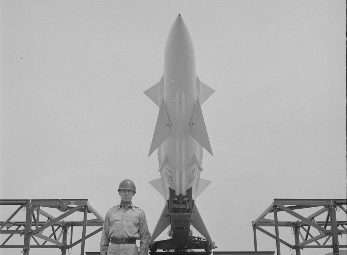 an unidentified American soldier stands under an anti-aircraft missile launcher at a Project Nike