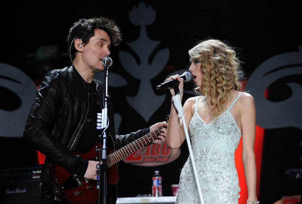 Taylor Swift and John Mayor look towards one another while singing on stage.
