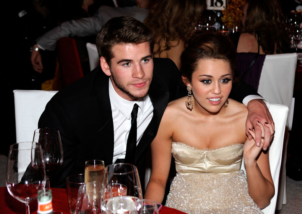 Liam Hemsworth wraps his arm around Miley Cyrus while the young couple holds hands.