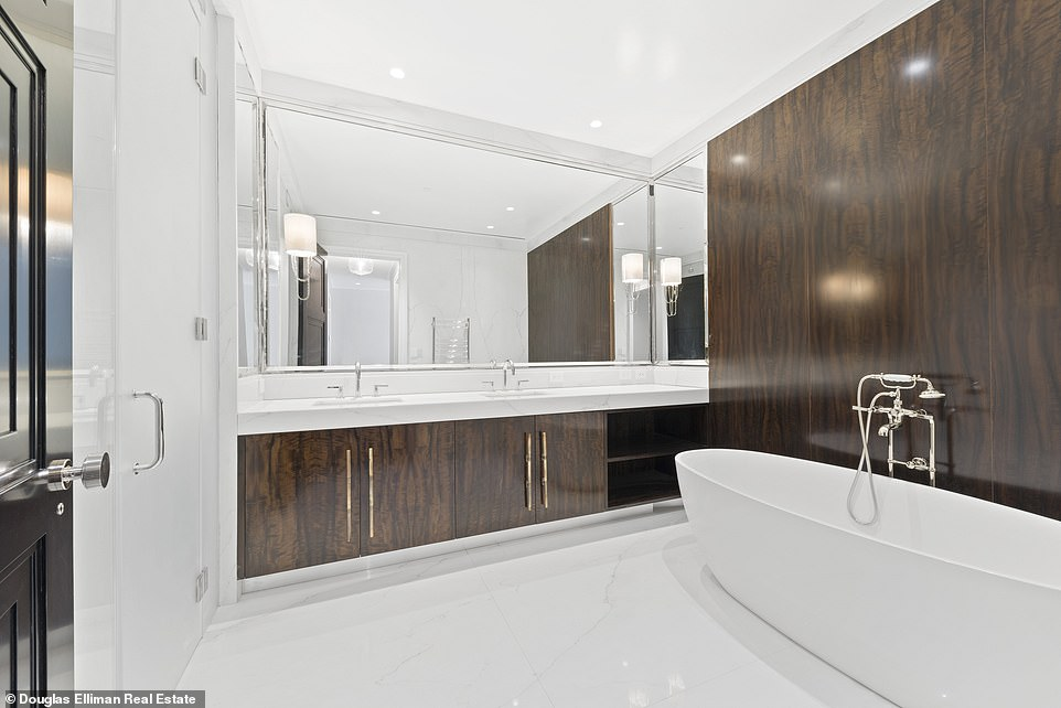 A large bathroom features double sinks, wood cabinets, and a modern oval sub with a handheld washing hose.
