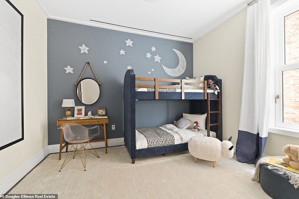 The room has a chalk-blue accent wall, a small desk, and designer bunkbed.