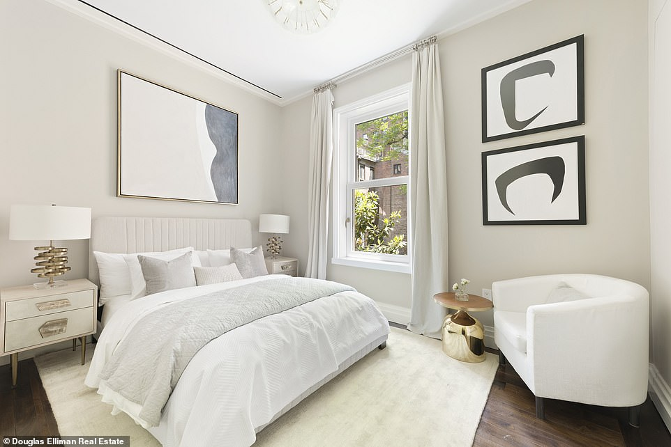 The bedroom shows a plush, large white bed with a matching reading chair beside a small accent table.