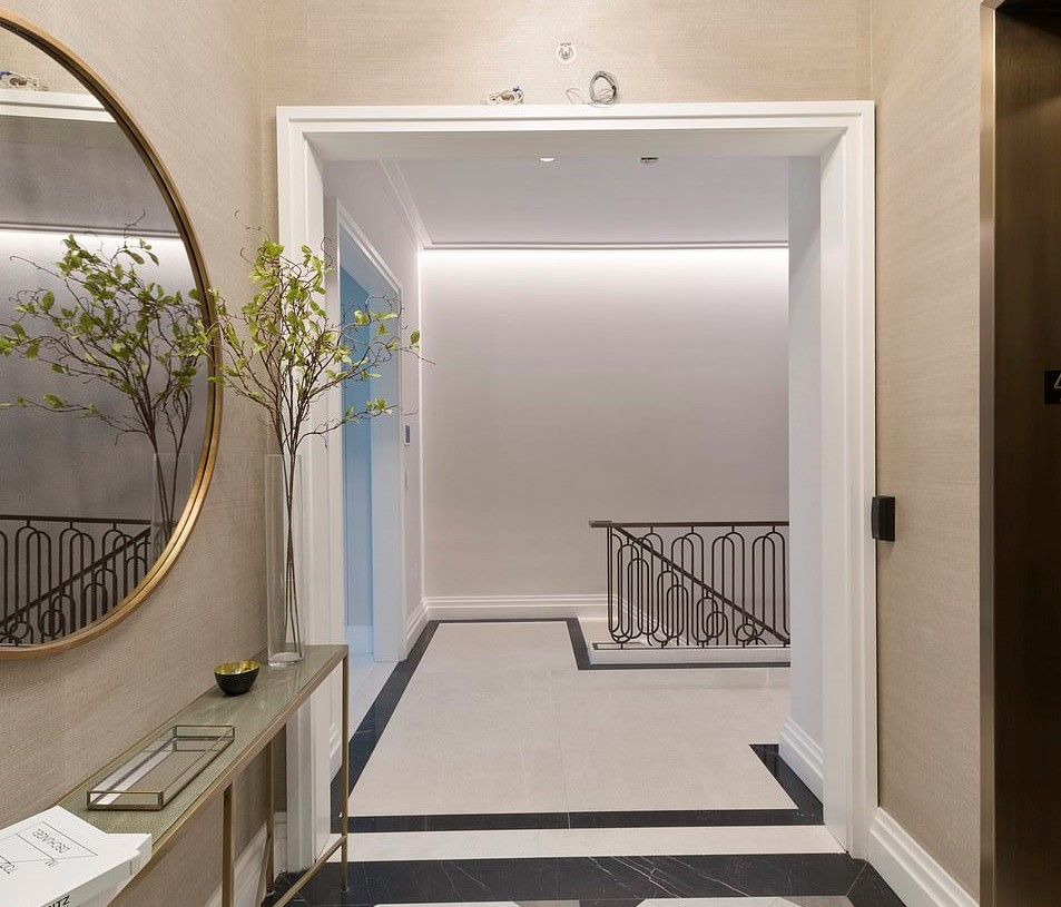 The elevator is to the right, in front of a mirror, entryway table, and modern chandelier.