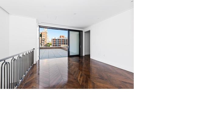 Hardwood floors line a bare space shapped by white walls and a huge sliding glass door, beyond which skyscrapers are in view.