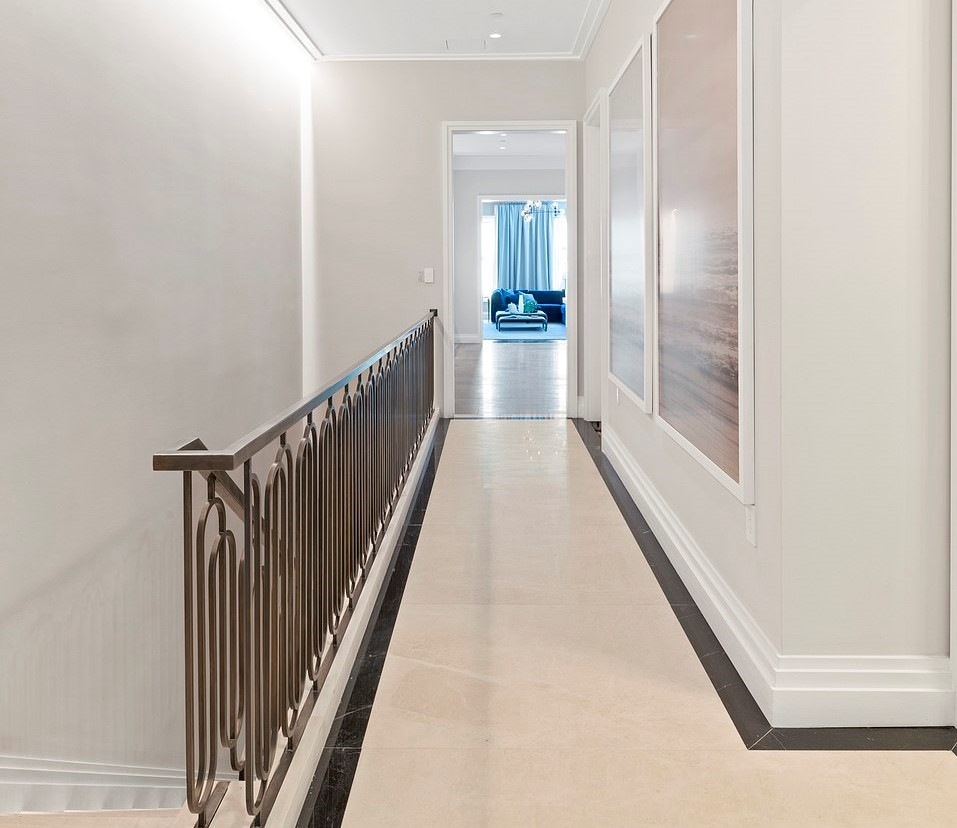 A spacious hallway with large canvas paintings on its wall across a stair railing leads into a large room.